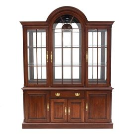 Pennsylvania House China Cabinet: A traditional style contemporary china cabinet by Pennsylvania House, in cherry. It has an upper hutch with an arched top, glass paned doors, and a mirrored interior back surface. The hutch has six adjustable/removable glass shelves with plate grooves, with two longer shelves to the center and two shorter ones to each side. The base of the piece features a central drawer with a black laminate hinged lid, and a felted silverware holder to the interior. Below this and to either side are cabinet spaces, with one adjustable/removable wood shelf each. There are lights mounted to the interior of the upper hutch, controlled by a dimmer switch, which were working at the time of cataloging.