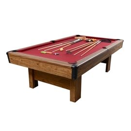 "Windsor Slate Billiard Table and Accessories: A Windsor slate billiard table and accessories. This traditional pool table features a Windsor red felt playing field, an oak laminate top rail with imitation mother-of-pearl inlay sights, and black acrylic pockets, being raised on square columnar legs. The table comes complete with pool balls, six pool cues, a bridge stick, two triangles and a wall mounted storage rack. The pool table is marked ""4 × 8 Slate Windsor"" with labels to the base."