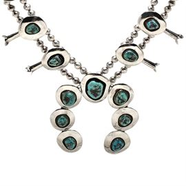 Sterling Silver Turquoise Squash Blossom Necklace: A sterling silver turquoise squash blossom necklace. The hand-crafted necklace is by an anonymous artist and features bezel set freeform turquoise cabochon stones with hollow sterling beads and sterling squash blossom bead accents.
