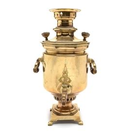 Antique Russian Brass Samovar: A turn of the century Russian brass samovar. The samovar features a barrel-shaped reservoir in polished brass, having turned wood handles and knobs, with an open steam vent to top and decorative brass spigot key. The tin lined samovar rests on a square self footed base and bears markings and medallion stamps from the Russian imperial maker Batesheva, with additional stamped awards and exhibition medals to the front and base. Samovars were first introduced to Russia during the mid-1700s, becoming an important center of cultural life.