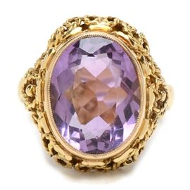 14K Yellow Gold Amethyst Ring: A 14K yellow gold amethyst ring. This ring features a bezel set 6.82 cts faceted amethyst stone in a fancy twisted wirework setting.