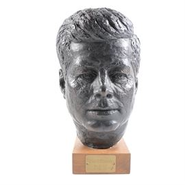 "Austin Reproductions Signed Schillaci John F. Kennedy Bust: An Austin Reproductions signed Schillaci John F. Kennedy bust. The piece is composed of resin and sits on a wooden base with four rounded felt pads along the underside. It depicts the bust of John F. Kennedy with a black finish. Under the bust, along the wooden base, is a brass place that reads ""John F. Kennedy May 29, 1917 Nov. 22, 1963"" and is signed along the back of the bust ""Schillaci""."