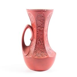 "1940s McCoy ""Daisy"" Vase: A 1940's McCoy Daisy vase. This red vase features an embossed daisy pattern and handle to one side. The underside of the vase is incised with model number and maker's mark, ""619 McCoy USA."""