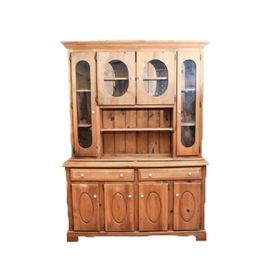 Vintage Pine China Cabinet: A vintage pine china cabinet. This rectangular top cabinet with molded trim features two central cabinet doors opening to a single shelf above an open shelf flanked by two larger cabinet doors opening to two shelves. The cabinet doors feature oval shaped clear glass panels and white knob handles. The cabinet sits on a rectangular top lower base featuring two aligned drawers over four cabinet doors terminating on ogee bracket feet. The cabinet doors open to a single shelf. There are no visible maker's marks.