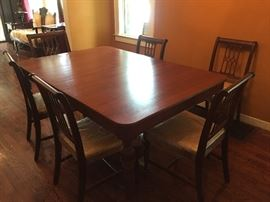 Antique family dinner table with reupholstered chairs.