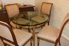 Glass and heavy brass table and four elegant dining chairs.