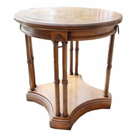 Regency Style Accent Table: A Regency style accent table. This piece features a light walnut stain. The circular top has bookmatched veneers, with a beveled edge and a contoured apron. Brass-toned rings accent the top blocks above the four pairs of faux bamboo legs. The legs are fixed to a concave square base.