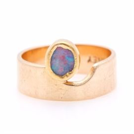 """Forney Goldsmiths 14K Yellow Gold Opal Ring: A 14K yellow gold opal ring by Forney Goldsmiths of Bloomington, Indiana. This ring features a smooth band with a notch cut out just to the right of a bezel set opal cabochon. The inside band is stamped """"14K, Forney""""."""