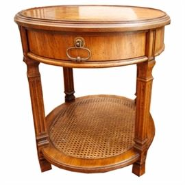 Oak Accent Table with Caned Shelf: An oak accent table with caned shelf and burled wood veneer top. This table features a circular shape with a drawer below the top surface that rises on fluted legs connected by a shelf stretcher. The piece is unmarked.