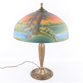 Antique Art Nouveau Reverse Painted Lamp: An antique Art Nouveau reverse painted table lamp. The lamp features a round reeded finial above a dimpled glass shade featuring a painted underside of a pastoral scene of shepherds with sheep. The lamp features a reeded brass body with two sockets and a pull chain. The lamp cord features a Bakelite plug.