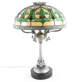 Art Nouveau Tiffany Style Leaded Glass Lamp: An Art Nouveau Tiffany style leaded glass lamp. The lamp features four sockets beneath a fixed shade with a filigree crown to a leaded glass shade comprised of cream and green glass with crimson jewel accents and an iron rim. The body features acanthus leaf accents to a round wooden base with an in cord switch.