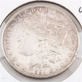 1884 S Silver Morgan Dollar: An 1884 S silver Morgan dollar. Designer: George T. Morgan. Mintage: 3,200,000. Metal content: 90% silver, 10% copper. Diameter: 38.1 mm. Weight: approximately 26.7 grams. Circulated. Good condition. The coin appears to have been cleaned.