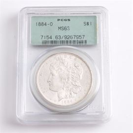 Graded MS-63 (By PCGS) 1884 O Silver Morgan Dollar: An encapsulated and graded MS-63 (By PCGS) 1884 O silver Morgan dollar. Designer: George T. Morgan. Mintage: 9,730,000. Metal content: 90% silver, 10% Copper. Diameter: 38.1 mm. Weight: approximately 26.7 grams. Very good condition.