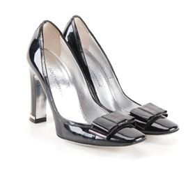 Dolce & Gabbana Patent Leather Heels: A pair of patent leather heels by Dolce & Gabbana. These heels showcase a black patent leather exterior and are accented with bows to the vamp. They also feature silver tone soles and a gold tone accent to the heels. They are a size 36 and are labeled with brand markings to the soles. Made in Italy.