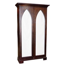 Floor Cabinet With a Wire Mesh and Fabric Windows: A floor cabinet with a wire mesh and fabric windows. This cabinet has arch shaped windows with a mire mesh and a fabric backing. The cabinet features a mahogany stained finish and rests on bracket feet.