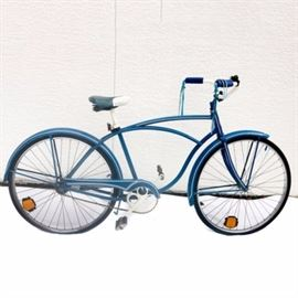 Blue Vintage Schwinn Bike with Bell: A vintage Schwinn bicycle. This bike features white walls on the tires, white accents, a bell, and cruiser style. The piece also showcases a blue finish and blue and white seat.