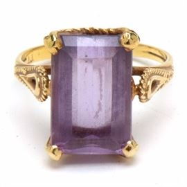 Vintage 18K Yellow Gold Amethyst Ring: A vintage 18K yellow gold amethyst openwork ring comprising a center prong set rectangular faceted cut amethyst gemstone, estimated at 5.40 cts with roped accents and a bright polish finish.