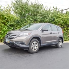 2012 Honda CRV LX: A 2012 Honda CRV LX with black interior. Odometer reads 86,255 miles. This Titanium color mid-size 4 door SUV features an i-Vtec 2.4 Liter DOHC four-cylinder engine and five-speed automatic transmission. It also has a black interior, air conditioning, alloy wheels, AM/FM CD stereo system, cruise control, power locks and windows, USB audio interface and rear wide-view camera. There is a dent on the front passenger-side bumper and smaller dent near the gas tank.
