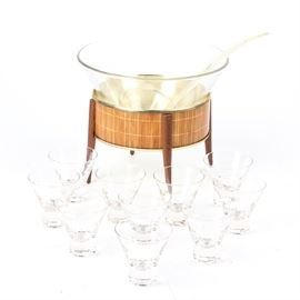 Mid Century Modern Punch Bowl Set: A mid century punch bowl set. This set consists of a cone shape glass punch bowl with ten matching cups. It sits on a round brass and faux bamboo base with four tapered wood legs and comes with a clear plastic punch bowl ladle.