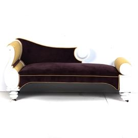 Upholstered Fainting Couch: An upholstered fainting couch. This beautiful piece is upholstered in a gold and royal purple fabric and features a white painted wooden frame. The couch rests on bun feet with castors. Unmarked.