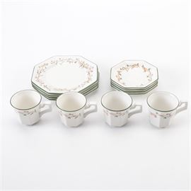 "Johnson Brothers"" Eternal Beau"" Tableware: A selection of Johnson Brothers Eternal Beau tableware. This selection includes twelve pieces featuring a pink flower and vine design interwoven with a tan ribbon and green trim. The base of each piece is marked ""Johnson Bros Since 1883 Made In England""."