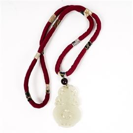 Chinese Carved Jadeite Jade Pendant: A Chinese carved and pierced jade pendant, dangling from a round, dark red bead above, on a necklace of silk fabric over cording. The fabric covering the cording is dark red, with sections of lighter patterned fabric at intervals. Not marked.
