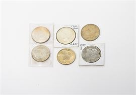 Six Liberty Silver Dollars: A grouping of six Liberty silver dollars. The coins include 1879S, 1881, 1883 and 1887 Morgan dollars; and 1922 and 1924 Peace dollars. The Morgan dollars were designed by George T. Morgan, the Peace dollars by Anthony de Francisci. Composition 90% silver, 10% copper. All 38.1 mm diameter and 26.73 grams at issue. Condition various, all circulated. Please preview for your own personal assessment.