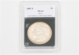"""1882-S Morgan Silver Dollar: An 1882-S Morgan silver dollar. The coin features a left facing profile of Lady Liberty on the obverse. The reverse depicts a bald eagle clutching an olive branch in one talon and a bundle of arrows in the other, surrounded by the text """"United States of America"""", """"One Dollar"""", and """"In God We Trust"""". Designer: George T. Morgan. Mintage: 9,250,000. Metal Content: 90% silver, 10% Copper. Approximate diameter: 38.1 mm. Approximate weight: 26.73 grams. Condition: Good. Please preview for your own personal assessment."""