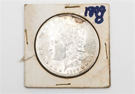 """1899-O Morgan Silver Dollar: An 1899-O Morgan silver dollar. The coin features a left facing profile of Lady Liberty on the obverse. The reverse depicts a bald eagle clutching an olive branch in one talon and a bundle of arrows in the other, surrounded by the text """"United States of America"""", """"One Dollar"""", and """"In God We Trust"""". Designer: George T. Morgan. Mintage: 12,290,000 Metal Content: 90% silver, 10% Copper. Approximate diameter: 38.1 mm. Approximate weight: 26.73 grams. Condition: Very good. Circulated. Please preview for your own personal assessment."""