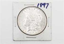 """1897 Uncirculated Morgan Silver Dollar: An 1897 Uncirculated Morgan silver dollar. The coin features a left facing profile of Lady Liberty on the obverse. The reverse depicts a bald eagle clutching an olive branch in one talon and a bundle of arrows in the other, surrounded by the text """"United States of America"""", """"One Dollar"""", and """"In God We Trust"""". Designer: George T. Morgan. Mintage: 2,822,000. Metal Content: 90% silver, 10% Copper. Approximate diameter: 38.1 mm. Approximate weight: 26.73 grams. Condition: Very good. Uncirculated. Please preview for your own personal assessment."""