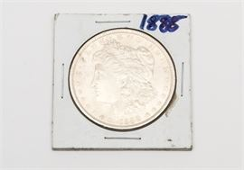 """1888 Morgan Silver Dollar: An 1888 Morgan silver dollar. The coin features a left facing profile of Lady Liberty on the obverse. The reverse depicts a bald eagle clutching an olive branch in one talon and a bundle of arrows in the other, surrounded by the text """"United States of America"""", """"One Dollar"""", and """"In God We Trust"""". Designer: George T. Morgan. Mintage: 19,183, 000. Metal Content: 90% silver, 10% Copper. Approximate diameter: 38.1 mm. Approximate weight: 26.73 grams. Condition: Good. Please preview for your own personal assessment."""