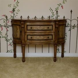 French Provincial Style Reproduction Sideboard: A French Provincial style reproduction sideboard. Designed with painted vine medallion to scallop top which continue to side doors and drawer fronts. Grooved columns flank the front above turned column legs. Sides feature bowed doors with beaded panel and drop pulls. Two stacked drawers to center.