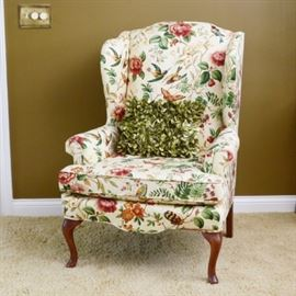 Custom Upholstered Wing Back Chair: A custom upholstered wind back occasional chair features arched top with scalloped wing, rolled arms and loose seat cushion. Cabriole style legs to front and flared to back. Upholstered in a bright floral with hummingbirds and butterflies. A green accent pillow is included.