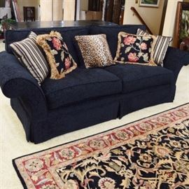 Custom Upholstered Sofa with Accent Pillows: A custom upholstered black sofa with accent pillows. A traditional style sofa with straight back and rolled arms, loose seat and back cushions and flat front skirt. Upholstered in a tone on tone floral printed fabric. Also included are five accent pillows.
