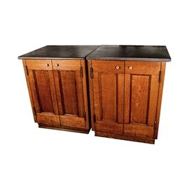 Stone-Top Oak Cabinets: A pair of stone-top oak cabinets. This matching pair have brown stone tops, resting above two recessed panel doors to the front of each. The doors open with brass-toned knobs to reveal storage shelves within. The cabinets stand on plinth bases.