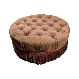 Burgundy and Gold Circular Ottoman: A burgundy and gold circular ottoman. This circular ottoman features a woven burgundy and gold upholstery, with button tufting to the top. The bottom is finished with a burgundy fringe. For coordinating pieces, see items 17STL041-002 and 17STL041-003.