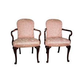 Pair of Queen Anne Style Armchairs: A pair of Queen Anne style armchairs with pink toned upholstery. These chairs feature a rounded crest rail over a rectangular back attached to the rounded square seat that is flanked by the flared and curved arms. The chair rises on cabriole legs with carvings to the knees and terminates on pad feet.