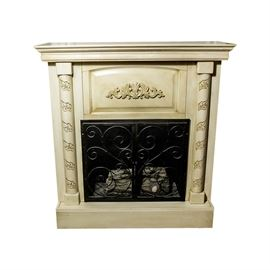 Electric Fireplace/Mantel: An electric fireplace with mantel surround. This piece comprises a creme painted carved mantel with a metal screen. A loose block resembling a stack of logs inside.