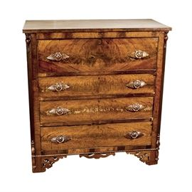Antique Chest of Drawers: An antique chest of drawers. This piece features figured walnut veneers. Below the rectangular top are four hand dovetailed drawers, opening with carved flower and leaf pulls. The drawers are flanked by turned facade stiles, ending in square feet accented with pierced spandrels.