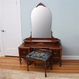 Vintage Art Deco Style Mahogany Vanity With Mirror and Bench: A vintage Art Deco style mahogany vanity. This vanity features a rectangular top with beveled edge over a knee hole opening with bowed edge and scalloped apron flanked by twin drawers with dovetail joinery, brass tone decorative plates and ring handles, and applied S-scroll detail. Each drawer is flanked by reeded stiles and sits above a scalloped apron with applied scroll carving. The vanity rises on turned cylindrical feet. Also includes a top piece with an attached arched mirror featuring a wooden pediment and burl veneer corner supports over a demilune base with a central drawer. The vanity bench includes an upholstered rectangular top and low raised back with turned crest rail rising on turned legs joined by an H-stretcher. There are no visible maker's marks.