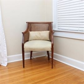 Vintage Caned Barrel-Back Chair: A vintage caned barrel-back chair. This chair features a mahogany frame with a flared crest and slightly rolled arms; its back and arm supports are caned. Its seat is upholstered in a cream tone floral fabric with nailhead trim. It rises on tapered legs.
