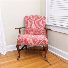 Zebra Print Louis XV Style Armchair: A Zebra print Louis XV Style Armchair. This pink toned zebra print chair features a serpentine shaped crest rail over a rectangular back and square seat with serpentine shaped front apron and nailhead trim. The chair rises on cabriole legs with carvings to the knees, connected by a turned H stretcher and terminating on pad feet.