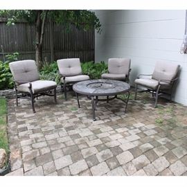 Set of Patio Chairs and Fire Pit: A set of four patio chairs and a fire pit. These chairs feature scrolled arms that rise on curved legs. Included with the chairs are back cushions with button tufting and square seat cushions. The fire pit features curved legs connected by a stretcher.