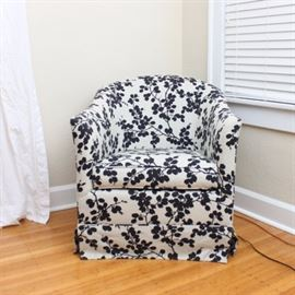 Upholstered Rocker by Crate & Barrel: An upholstered rocking armchair by Crate & Barrel. Features a rounded back, padded arms, and removable seat. The entire chair is upholstered in a white fabric with a bold black foliate pattern and includes a skirt.