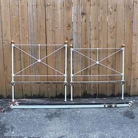 Wrought Iron Twin Size Bed Frame: A vintage wrought iron twin-size bed frame. Includes a headboard and footboard, each with a white painted metal frame with an X design and brass toned orb finials. Also, includes a pair of metal side rails.