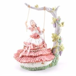 "Dresden Style ""Lace"" Porcelain Figurine: A Dresden Style ""Lace"" Porcelain Figurine. This porcelain figurine is in the form of a woman wearing a pink billowy crinoline gown sitting on a swing under a tree branch. No makers mark is noted."