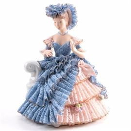 "Dresden Lace Style Porcelain Figurine: A Dresden Lace style porcelain figurine. This porcelain figurine is in the form of a woman wearing a billowy crinoline dress and matching hat sitting on a settee. The base is marked to the underside ""Mary Merkle 1986."""