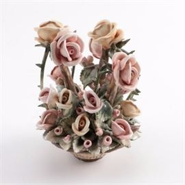 Ceramic Roses in Basket Figurine: A ceramic roses in basket figurine. The piece features a muted palette in pink, deep green, and cream and depicts basket filled with roses and leaves throughout. It is marked to the underside.