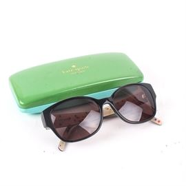 """Kate Spade """"Grady"""" Polarized Cat-Eye Sunglasses: A pair of Kate Spade """"Grady"""" polarized cat-eye sunglasses. These sunglasses feature black frames with smokey-tinted lenses. They are marked """"grady/p/s 807p ra140 1-6"""" to the interior and """"Kate Spade – New York"""" along the side. Includes a green Kate Spade sunglasses case."""