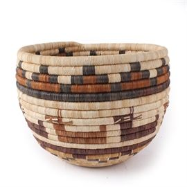 """Handwoven Hopi Style Coil Basket: A handwoven Hopi style coil basket. It features a tightly coiled shape in gradient brown hues with images of antelope woven in. Presents with a label that reads """"Hopi Coil Basket """"Antelopes"""" Weaver… Karen Lomahongua"""". In the Hopi culture, woven baskets not only serve utilitarian purposes, but also are used in ceremonial contexts, and as a type of currency in trade."""